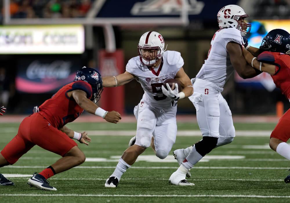 Christian McCaffrey stiff arming a Wildcat