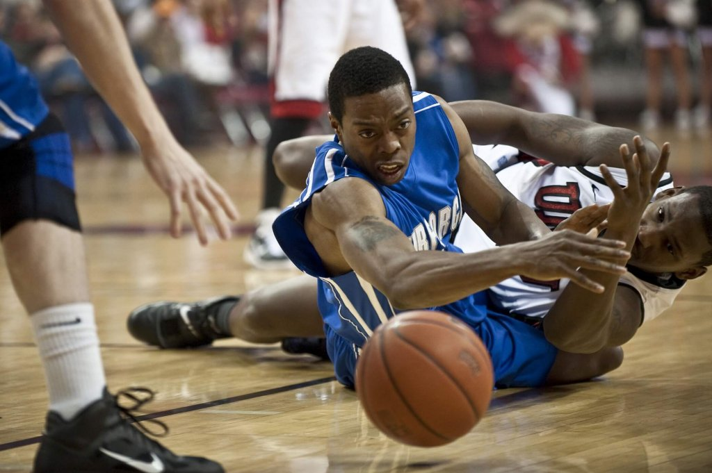 An Air Force and UNLV player reach for the ball.