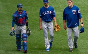 Mike Minor walking to the mound with Ranger teammates and coaches.