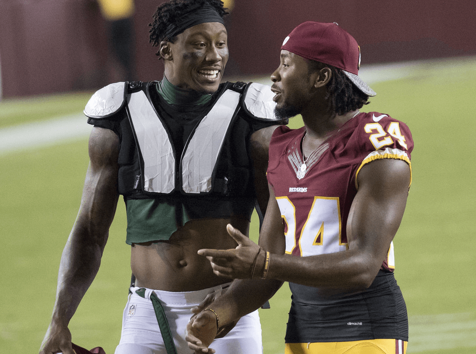 Josh Norman talks wit Brandon Marshall on the field.