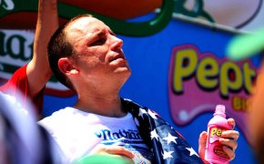 Joey Chestnut posing with titlle belt.