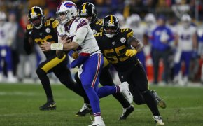 Buffalo Bills quarterback Josh Allen running with the ball and Pittsburgh Steelers linebacker Devin Bush pursuing him.