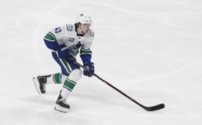 Vancouver Canucks defensemen Quinn Hughes skating in the middle of a NHL game.