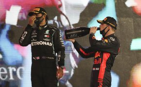 Mercedes driver Lewis Hamilton of Britain, left, and Red Bull driver Max Verstappen of the Netherlands stand on the winners podium in Abu Dhabi