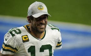 Green Bay Packers quarterback Aaron Rodgers smiling as he walks off the field.