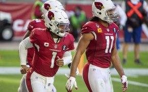 Arizona Cardinals quarterback Kyler Murray, and wide receiver Larry Fitzgerald walking on the football field.