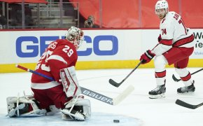 Detroit Red Wings goaltender Thomas Greiss blocking a shot from Carolina Hurricanes' Jaccob Slavin in an NHL game.