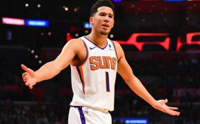 Devin Booker, arms out, not happy with a call