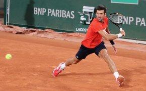 Novak Djokovic sliding to hit a backhand on clay
