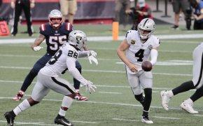 Las Vegas Raiders quarterback Derek Carr (4) hands off to Las Vegas Raiders running back Josh Jacobs (28).