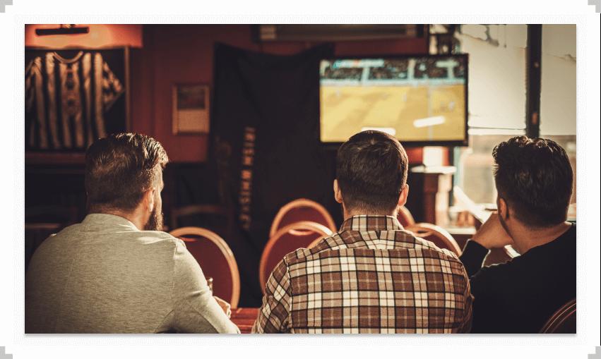 Three guys sitting at a bar watching TV