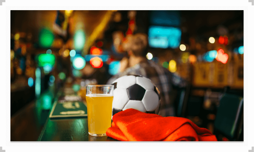Soccer ball and glass of beer on a bar table