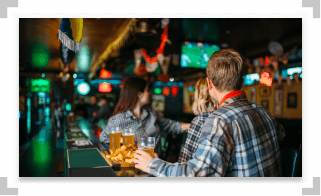 People sitting at a bar with drinks watching tv
