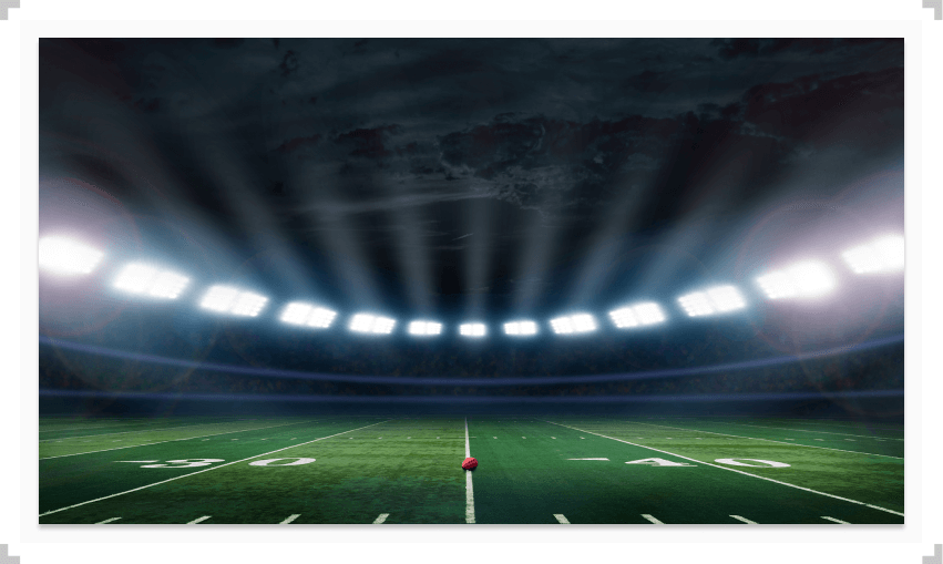 Empty football stadium with a football on the field