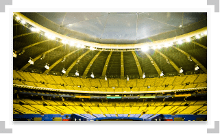 Large empty stadium with yellow and blue seats