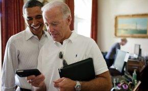 Joe Biden and Barack Obama looking at a smartphone