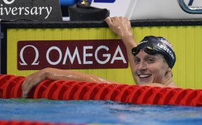 Katie Ledecky in the pool holding on to the edge