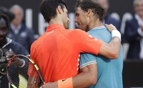 Rafael Nadal and Novak Djokovic hugging at the end of a tennis match.