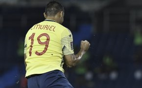 Colombia's Luis Muriel celebrating with fist pumps after scoring a goal.
