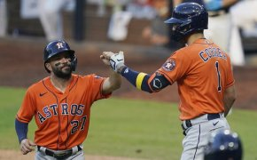 Houston Astros' Jose Altuve and Carlos Correa celebrating on the field after scoring a run.