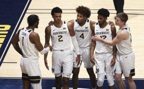 West Virginia's Derek Culver, Jalen Bridges, Miles McBride, Taz Sherman, and Sean McNeil all gather on the court during a NCAA men's basketball game.