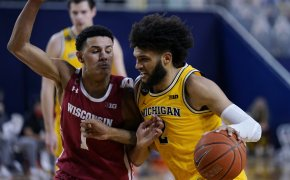 Michigan forward Isaiah Livers driving to the net against Wisconsin guard Jonathan Davis during a NCAA men's basketball game.