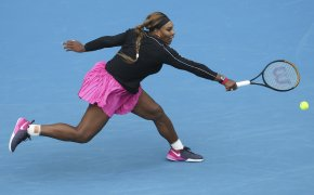 Serena Williams stretching to make a backhand return in a match.