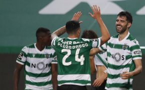 Luis Neto and Pedro Porro celebrating with high fives after their teammate scored the opening goal during a soccer match.