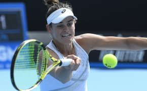 United States' Jennifer Brady stretching to make a forehand return against her opponent during a tennis match.