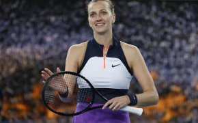 Petra Kvitova celebrating by clapping her racket after a tennis match win.