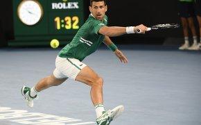 Novak Djokovic stretching to make a backhand return during a match at the 2021 Australian Open.