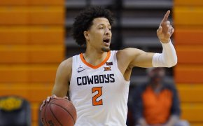 Oklahoma State guard Cade Cunningham calling a play dribbling up the court during a game.