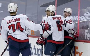 Washington Capitals' Nicklas Backstrom celebrating with teammates on the ice after scoring a goal during a NHL game.