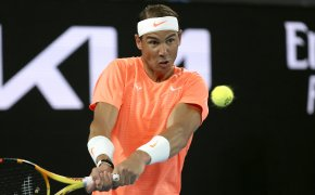 Rafael Nadal hitting a backhand return during a tennis match.