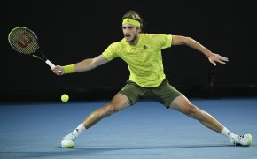 Stefanos Tsitsipas hitting a forehand return during a tennis match.