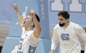 North Carolina forward Walker Kessler reacting and celebrating with his hands in the air during a NCAA men's basketball game.