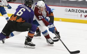 Nathan MacKinnon trying to get a shot off between two Arizona Coyote players during a NHL game.