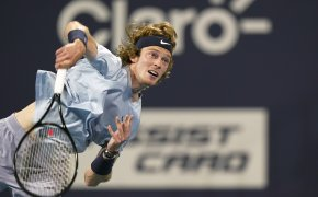 Andrey Rublev following through on a serve during a tennis match.