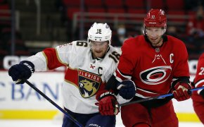 Florida Panthers' Aleksander Barkov battles on the ice for the puck against Carolina Hurricanes' Jordan Staal during an NHL game.