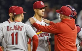Coach with hands on shoulder of Jack Flaherty, with teammates surrounding them