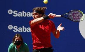Stefanos Tsitsipas hitting a forehand return during a tennis match.