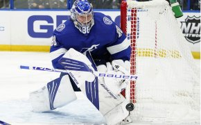 Andrei Vasilevskiy tight against goal post steering puck away