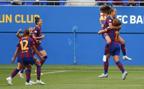 Barcelona players running and congratulated each other after scoring a goal during a soccer match.