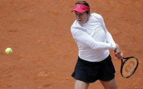 Anastasia Paulyuchenkova hitting a backhand return during a clay court tennis match.
