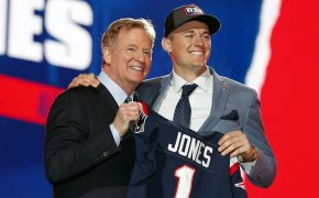 Alabama quarterback Mac Jones holding a team jersey with NFL Commissioner Roger Goodell after New England Patriots selected him in the draft.