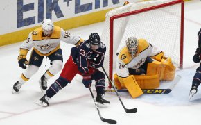Nashville Predators' Alexandre Carrier trying to stop Columbus Blue Jackets' Cam Atkinson from taking a shot during an NHL game.