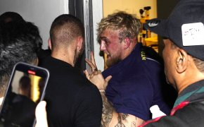 Jake Paul being pushed and held back from boxer Floyd Mayweather during a news conference.
