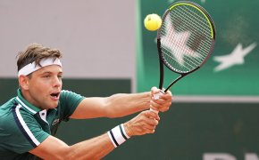 Filip Krajinovic hitting a return during a tennis match.