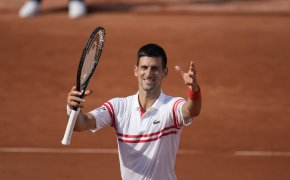 Novak Djokovic celebrating on the court after winning a match at the 2021 French Open.