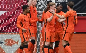 Netherlands players celebrating scoring a goal during a soccer match.